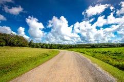 Asphaltstraße durch das grüne Feld und Wolken auf blauem Himmel stockfotos