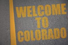 Asphaltstraße mit Textwillkommen zu Colorado nahe gelber Linie Lizenzfreie Stockfotografie