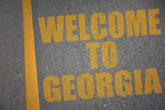 Asphaltstraße mit Textwillkommen zu Georgia nahe gelber Linie stockfotografie
