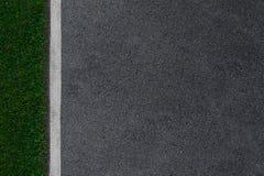Asphaltstraße mit weißen Linien und Hintergrund des grünen Grases lizenzfreie stockbilder