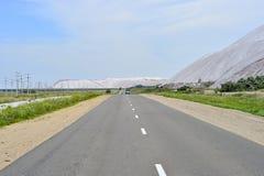 Asphaltstraße am Rand der Dumps der Bergwerke von Weißrussland, die Stadt von Soligorsk Lizenzfreies Stockbild