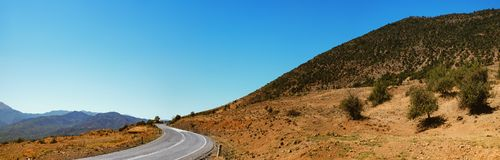 Asphaltstraße und Berge über blauem Himmel in Griechenland Lizenzfreie Stockbilder