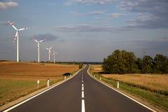 Asphaltstraße, welche entlang Wind millsin die Landschaft führt lizenzfreie stockbilder