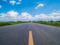 Asphaltstraße zwischen dem Getreidefeld und dem schönen blauen Himmel bewölkt lizenzfreies stockfoto