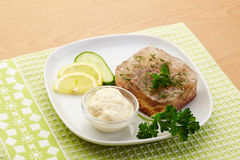 Aspic of beef on white plate with lemon, cucumber, horseradish and parsley. Food Stock Image