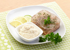 Aspic of beef on white plate with lemon, cucumber, horseradish and parsley. Food Royalty Free Stock Photography