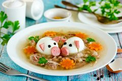 Aspic jellied pork meat holodets decorated with boiled eggs. Shaped funny pigs, carrot flowers and green parsley, traditional russian dish holodets for festive stock photos