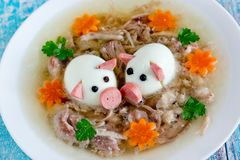 Aspic jellied pork meat holodets decorated with boiled eggs. Shaped funny pigs, carrot flowers and green parsley, traditional russian dish holodets for festive royalty free stock photography