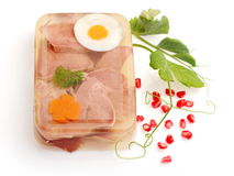 Aspic from meat decorated with egg, carrot... Aspic from meat decorated with egg, carrot, pomegranate and green pea over white background Stock Photos