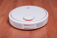 Aspirador blanco del robot en el polvo laminado de la limpieza del piso en sala de estar Tecnología electrónica elegante moderna  Fotos de archivo libres de regalías