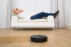 Aspirador de p30 robótico na frente do homem que relaxa Imagens de Stock
