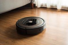 Aspirador del robot en el piso de madera, laminado Conceptos elegantes de la vida foto de archivo