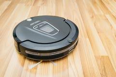 Aspirador del robot en el piso de madera laminado, robótico elegante casero imagen de archivo
