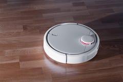 Aspirador del robot en el piso laminado, limpieza inalámbrica de la robótica casera elegante para simplificar el quehacer domésti imagen de archivo