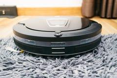 Aspirador del robot en la madera y la alfombra laminadas Imagen de archivo libre de regalías