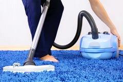 Aspirador en limpiador de los acción-hombres una alfombra. Fotografía de archivo