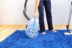 Aspirador en limpiador de los acción-hombres una alfombra. Imágenes de archivo libres de regalías
