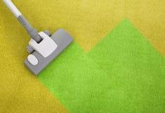 Aspirador en una alfombra verde Foto de archivo