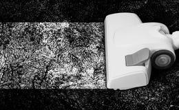Aspirador muy blanco en una alfombra muy negra fotos de archivo libres de regalías
