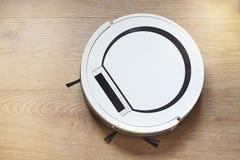 Aspirador robótico en el piso de madera Dispositivo moderno para limpiar fotos de archivo libres de regalías