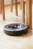 Aspirador robótico en la limpieza elegante del piso de madera laminado técnica fotos de archivo libres de regalías