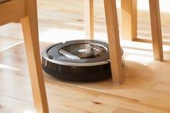 Aspirador robótico en la limpieza elegante del piso de madera laminado técnica foto de archivo