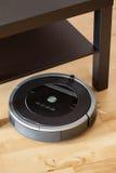 Aspirador robótico en la limpieza elegante del piso de madera laminado técnica imagen de archivo libre de regalías