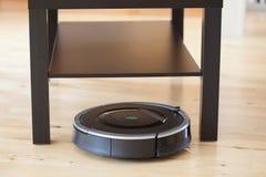 Aspirador robótico en la limpieza elegante del piso de madera laminado técnica fotografía de archivo