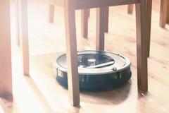 Aspirador robótico en la limpieza elegante del piso de madera laminado técnica imágenes de archivo libres de regalías