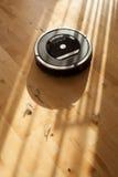 Aspirador robótico en la limpieza elegante del piso de madera laminado técnica imagen de archivo