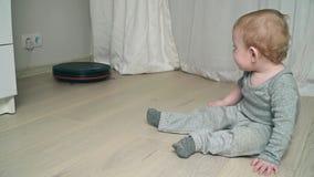 Aspirador robótico en piso con el bebé en el piso de madera metrajes