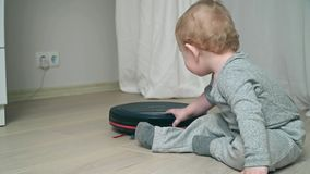 Aspirador robótico en piso con el bebé en el piso de madera almacen de metraje de vídeo