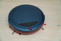 Aspirador robótico en piso de madera laminado Tecnología de limpieza elegante fotografía de archivo