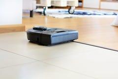 aspirador robótico en piso tejado y de madera brillante Foto de archivo