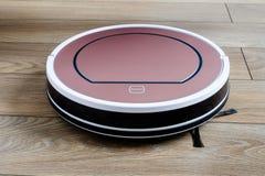 Aspirador robótico en tecnología de limpieza elegante del piso de madera fotografía de archivo