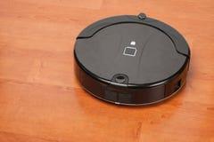 Aspirador robótico que trabaja en piso de madera laminado economía doméstica elegante de la tecnología de limpieza fotografía de archivo