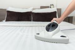 Aspirapolvere dell'acaro che usando il materasso del letto di pulizia immagine stock
