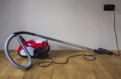 Aspirapolvere moderno rosso con cavo elettrico nero su PA di legno Fotografie Stock