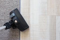Aspirapolvere moderno sopra tappeto ed il pavimento di parquet di legno Fotografie Stock