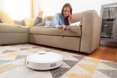 Aspirapolvere robot che pulisce la stanza fotografia stock libera da diritti