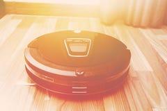 Aspirapolvere robot sul pavimento di parquet di legno, vuoto astuto, nuovo Fotografia Stock