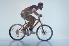 Aspirated guy with beard cycling in urban place Royalty Free Stock Photos