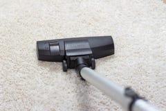 Aspirateur étant employé pour nettoyer à l'aspirateur un tapis Image stock