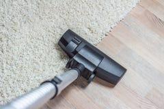 Aspirateur étant employé pour nettoyer à l'aspirateur un tapis Photographie stock