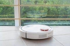 aspirateur blanc de robot nettoyant à l'aspirateur le plancher de tuiles, se reflétant dans la fenêtre panoramique avec la barriè image libre de droits
