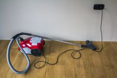 Aspirateur moderne rouge avec le câble électrique noir sur la PA en bois Images stock