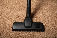 Aspirateur noir sur le tapis sale housework photo stock