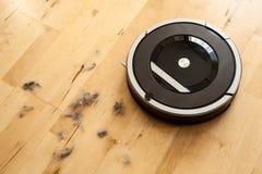 Aspirateur robotique sur le nettoyage futé de plancher en bois en stratifié technique photos stock