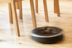 Aspirateur robotique sur le nettoyage futé de plancher en bois en stratifié technique Images libres de droits
