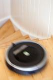 Aspirateur robotique sur le nettoyage futé de plancher en bois en stratifié technique Images stock